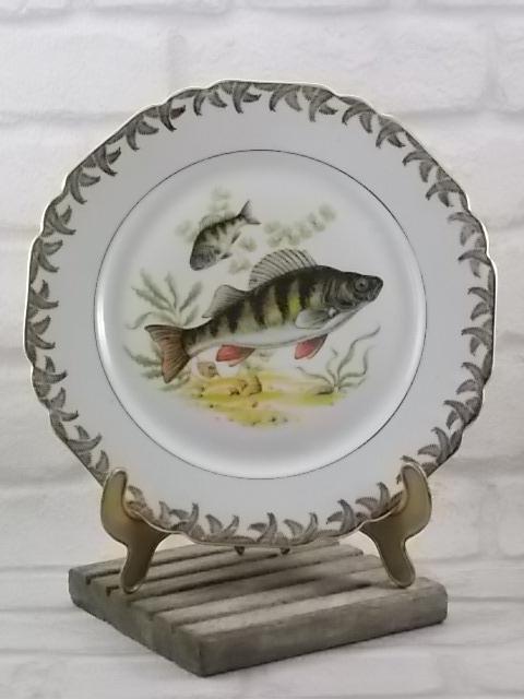 """Assiette """"Les Poissons"""" plate, en porcelaine Blanche. Décors sérigraphié polychrome, motif Animalier. Bordure feuillage stylisé et liseré en dorure. De Chadelaud Limoges."""