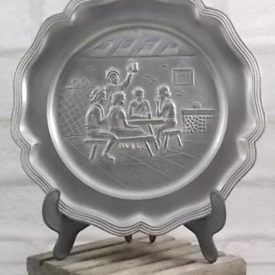 Assiette en Étain massif, minimum 95 %. Motif scène de Réunion familiale, bord chantourné mouluré.