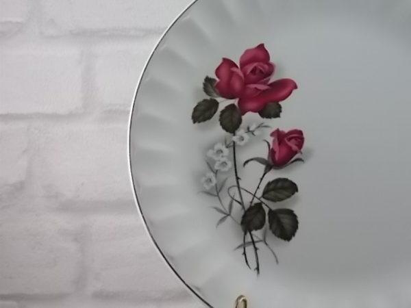 Assiette plate, en faïence Blanche, motif sérigraphié de Roses, bordure à facette festonnée souligné d'un liseré en dorure.