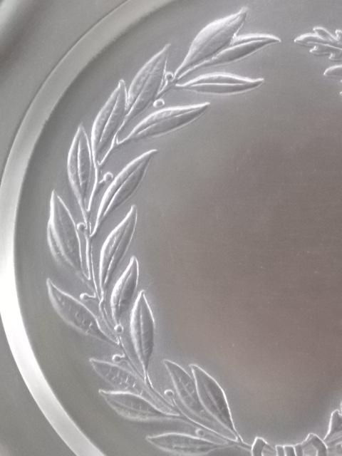 Assiette en Étain massif, minimum 96 %. Motif couronne de feuilles de Lauriers et Chêne?, bord chantourné.
