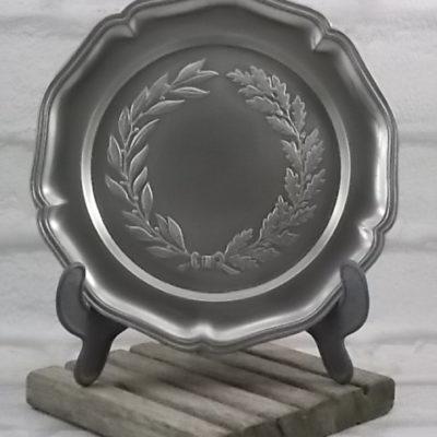 Assiette en Étain massif, minimum 95 %. Motif couronne de feuilles de Lauriers et Chêne, bord chantourné.