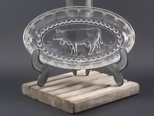 """Beurrier """"Vache"""" à godron ovale, en verre trempé moulé. Décors en médaillon perlé d'une vache dans son pré."""