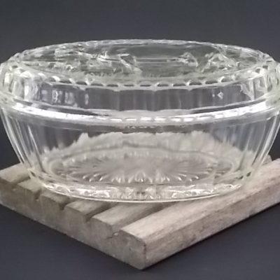 """Beurrier """"Vache"""" ovale en verre moulé épais. Décors du couvercle en relief, coté à facettes. Année 50."""