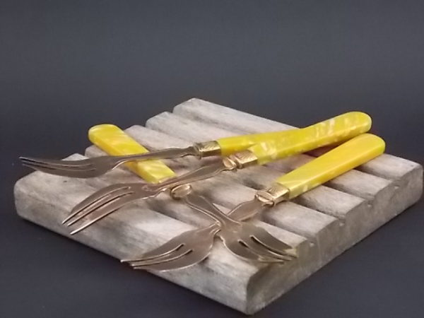 Fourchette à gâteaux, manche en Bakélite Jaune marbré. Virole avec encart motif Coquillage. Fourchette à 3 dents en métal doré cuivré.