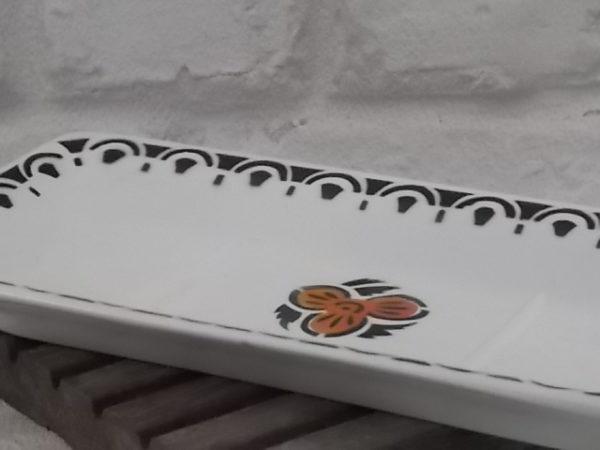 Porte savon, en faïence Blanche et frise géométrique Noir. Motif central de fleur stylisé Noir et Marron. de St Amandinoise de St Aman