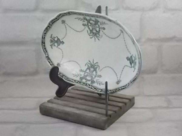 """Ravier """"Flambeaux"""", en faïence Ivoire et décors Vert. Motif Couronne à flambeaux croisés et guirlandes. De la manufacture de Longwy"""
