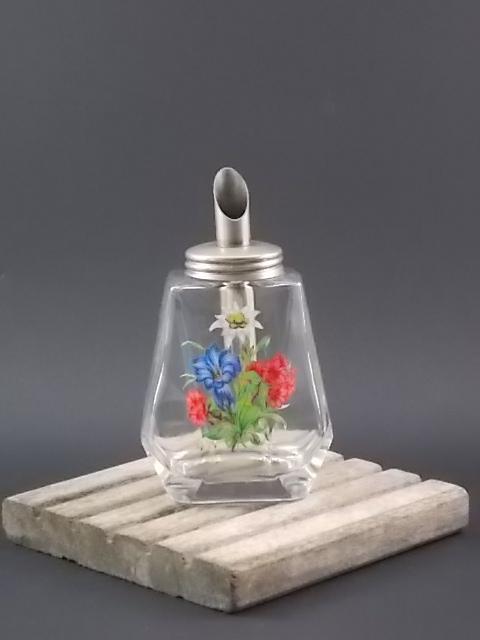 """Saupoudreuse à sucre """"Fleurs"""", à bec verseur. En verre moulé à facettes. Décors émaillé à motif floral. Bec verseur en métal. Années 50."""