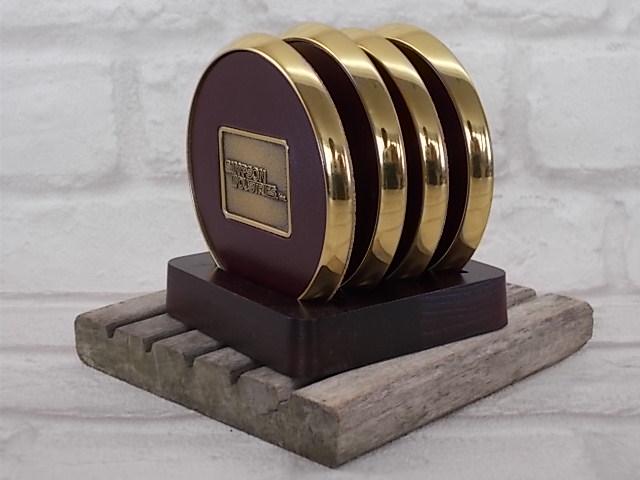 Coffret de 4 dessous de verre en métal dorée, revêtement vinyle simili cuir Marron et fond en liège, support de présentation en bois teinté Acajou.